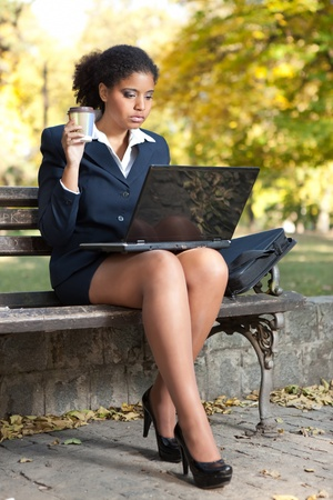 afro businesswoman with cup of coffee looking in laptop, outdoor photo
