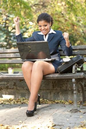 happiness businesswoman looking in laptop, outdoor photo