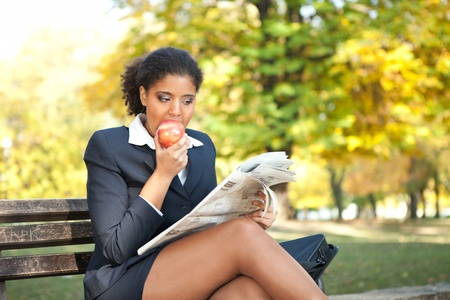 young businesswoman relaxing in park and eating apple photo