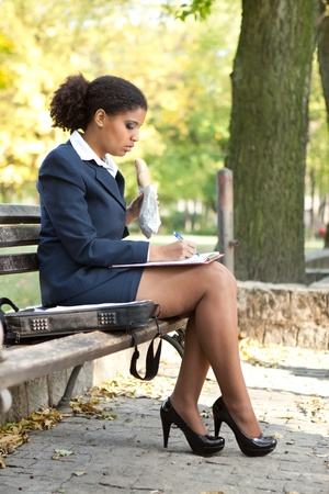 afro young businesswoman sitting on bench in park and making note photo