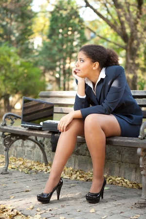 upset thinking businesswoman sitting on bench  photo