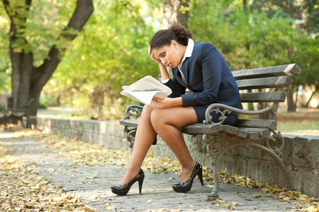 young worry businesswoman reading newspaper in park Stock Photo - 11503896