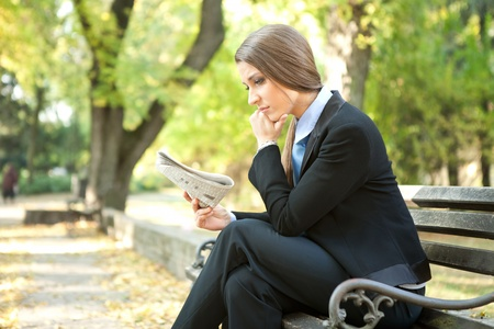 young thinking businesswoman reading newspaper , sitting on bench in park photo