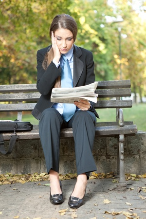 businesswoman reading newspaper with bad news, outdoor photo