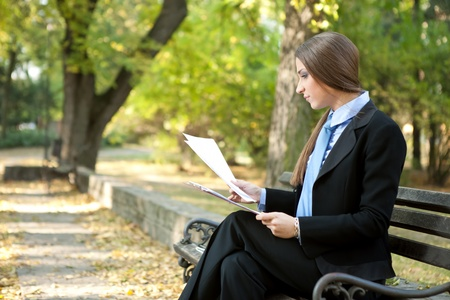 young businesswoman reading document in park photo
