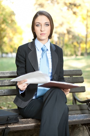 young businesswoman holding documents, outdoor photo