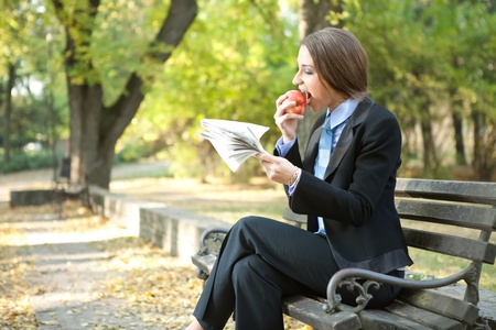 young businesswoman eating apple and relaxing in park  photo