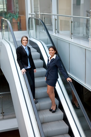 two attractive businesswomen on escalator in business center, mall or airport photo
