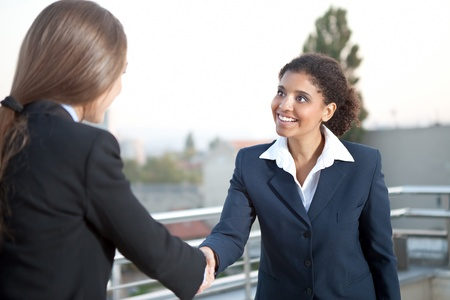 corporate responsibility: cheerful businesswomen shaking hands , business meeting