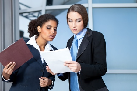 Two businesswomen working together,  looking in paperwork  photo