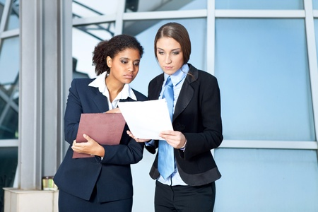 Two businesswomen looking in paperwork in corridor Stock Photo - 11508281