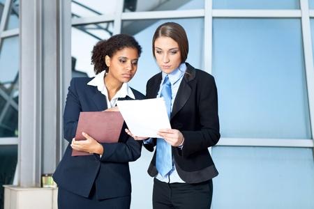 Two businesswomen looking in paperwork in corridor Stock Photo - 11508281