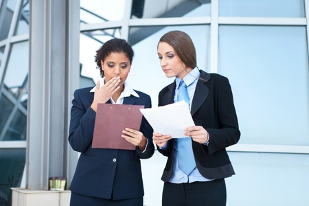 Two businesswomen working together with paperwork in hands photo