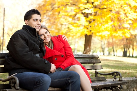 young affectionate couple embracing in park in autumn photo