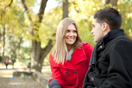 smiling young couple talking in park, girlfriend looking in boy photo