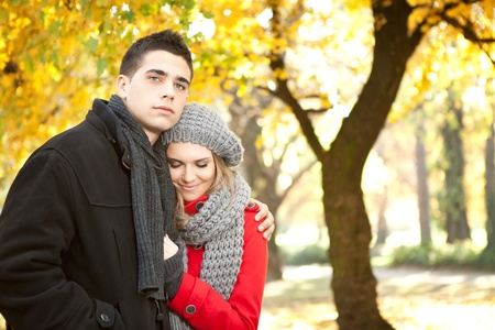 smiling girl in a warm embrace of her boyfriend, autumn park photo