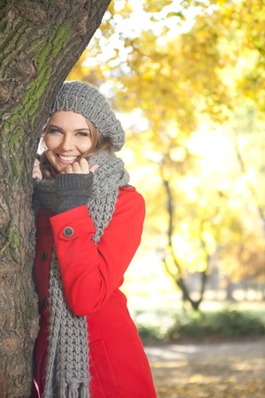 winter woman: young smiling woman in season warm clothing in autumn park Stock Photo