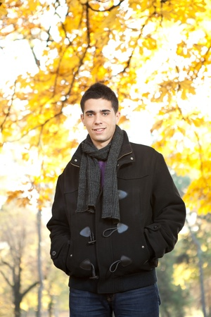 warm jacket: young man in black jacket in autumn park