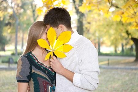 Junges Paar k�sst sich hinter gro�en Blatt, im Freien