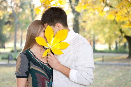 young couple kissing behind big leaf, outdoor photo