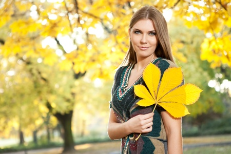 autumn beautiful girl holding big yellow leaf photo