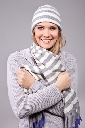 smiling girl wearing winter clothing: sweater, hat ... photo