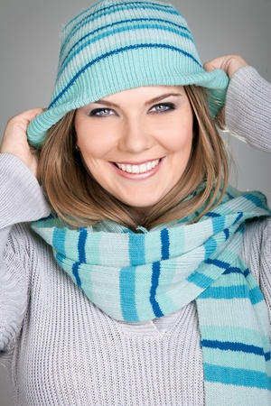 smiling woman having fun with her hat, winter time-concept photo