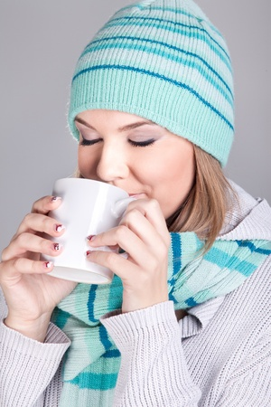 Beautiful happy smiling woman dressed with winter clothes holding a hot tea mug  photo