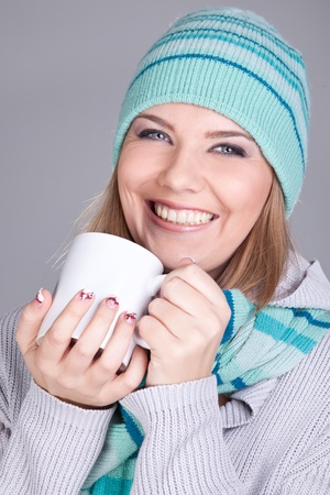 young smiling winter girl holding hot tea mug photo