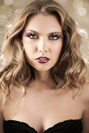 beautiful woman with blond curly hair and make-up on face photo