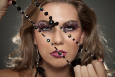 beauty woman with fashion make up pulling necklace photo