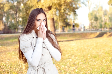 allergens:  Young girl with tissue having flu or allergy, outdoor Stock Photo