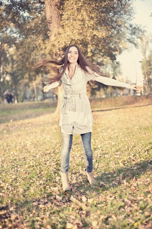 young woman having fun in autumn park, vintage style photo