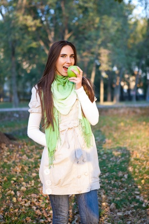 woman walking autumn park and eating apple photo