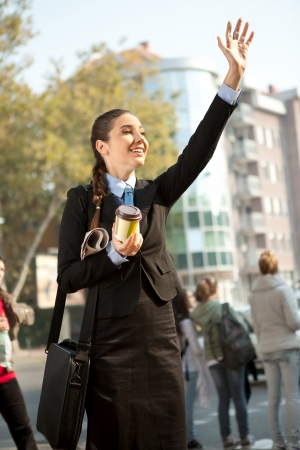 young businesswoman on street waving hello, business people photo