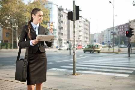 busy street: young businesswoman drinking coffee on street