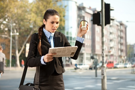 upset businesswoman reading bad news in newspaper, outdoor Stock Photo - 11516271