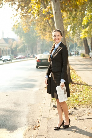 young smiling business woman with newspaper standing on street photo