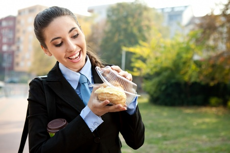 hungry businesswoman , smiling and looking in  donut, outdoor photo