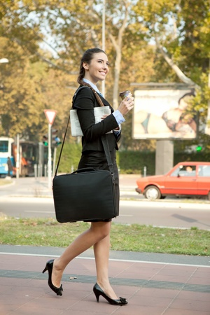 smiling, attractive businesswoman holding coffee and  walking on street photo
