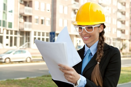 smiling female engineer with hard hat reading  blueprints, outdoor photo