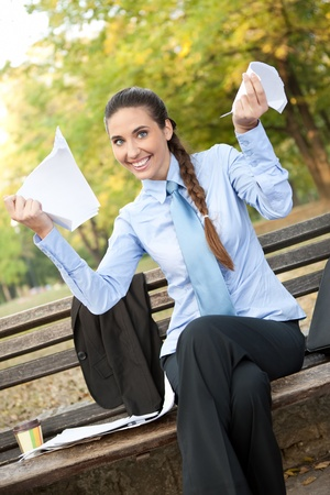 scrunch: smiling businesswoman with  tear  documents in hands, outdoor