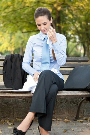 broken contract: Businesswoman tearing up documents on bench in park