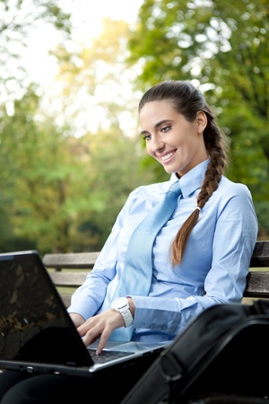smiling businesswoman typing on laptop, sitting on bench  in park  photo