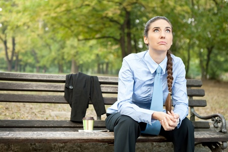 sad businesswoman  sitting on bench in park and looking up Stock Photo - 11516272