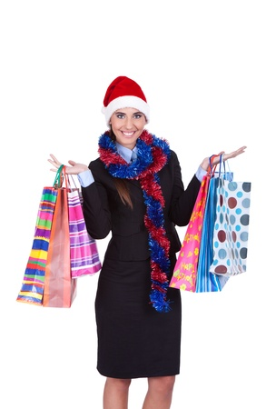 young smiling girl in Santa hat holding shopping bags, isolated over white background photo
