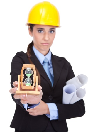 dissatisfied female architect holding clock and plans, time is running out photo