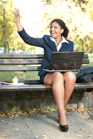 young businesswoman in park, smiling  afro woman  waving hello photo