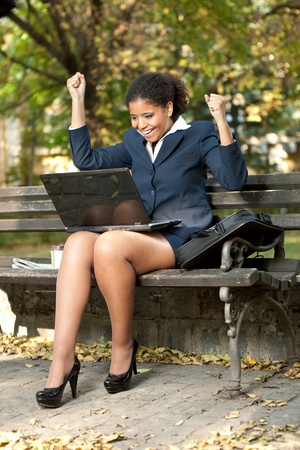 pretty successful business woman with her hands raised while working on laptop, outdoor photo
