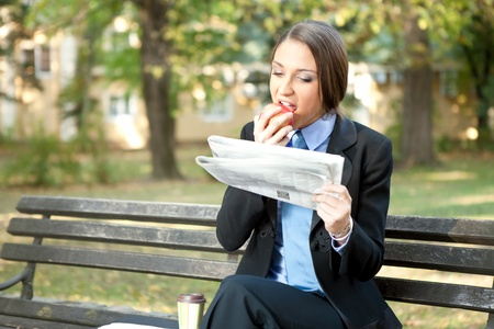 park bench: businesswoman on break eating apple and reading newspaper